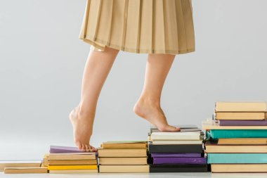 close up barefoot woman walking on aged books