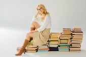 beautiful blonde woman in glasses sitting on pile of retro books