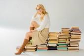 gyönyörű szőke nő ül a retro könyv halom szemüveg