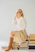 Fotografie krásná blondýnka v brýlích sedí na hromadě knih, retro