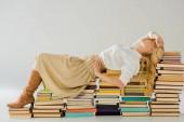 Fotografie krásná blondýnka v brýlích pózuje na retro knih