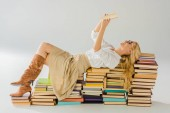 Photo beautiful blonde woman in glasses reading and laying on pile of retro books