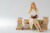 beautiful adult woman sitting on pile of retro books with white cup