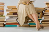 Photo close up of woman reading and sitting on pile of books