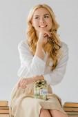 gyönyörű nő ül a megtakarítások elszigetelt szürke korsó-könyvek