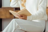 close up of elegant woman holding and reading book