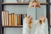 zblízka blond ženy, skrývá tvář za knihu