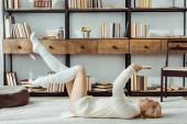 Fotografie usmívající se žena pokládání na koberci a čtení knihy