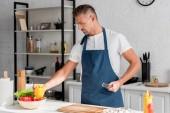 pohledný muž v zástěře na vaření v kuchyni doma