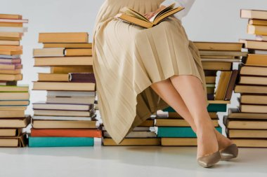 close up of woman reading and sitting on pile of books