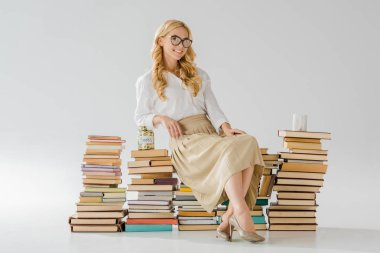 beautiful woman in glasses sitting on books with savings in jar and cup