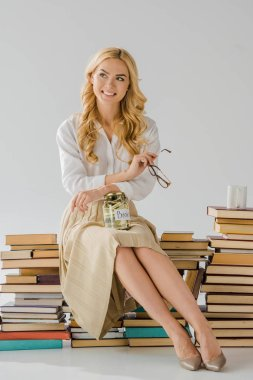 beautiful woman sitting on books with savings in jar and cup
