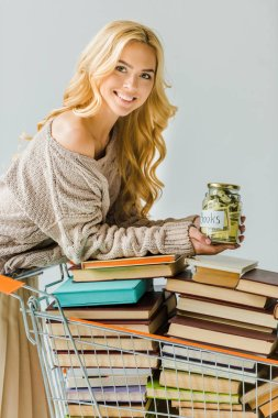 Beautiful woman with money in jar and retro book in shopping cart isolated on grey stock vector