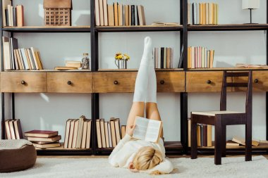 woman laying on carpet and reading book with legs on rack