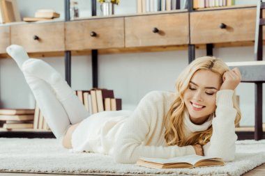 smiling woman laying on carpet and reading book