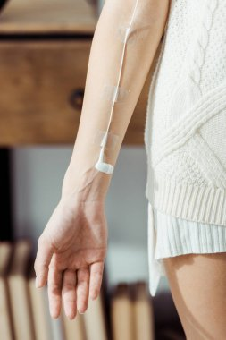 close up of female hand with white earphone like medical IV infusion, music concept