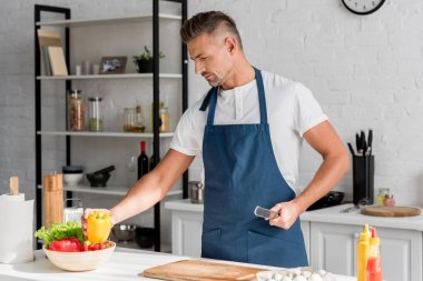 handsome man in apron cooking on kitchen at home