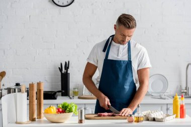 Mature man cutting meat for dinner in kitchen