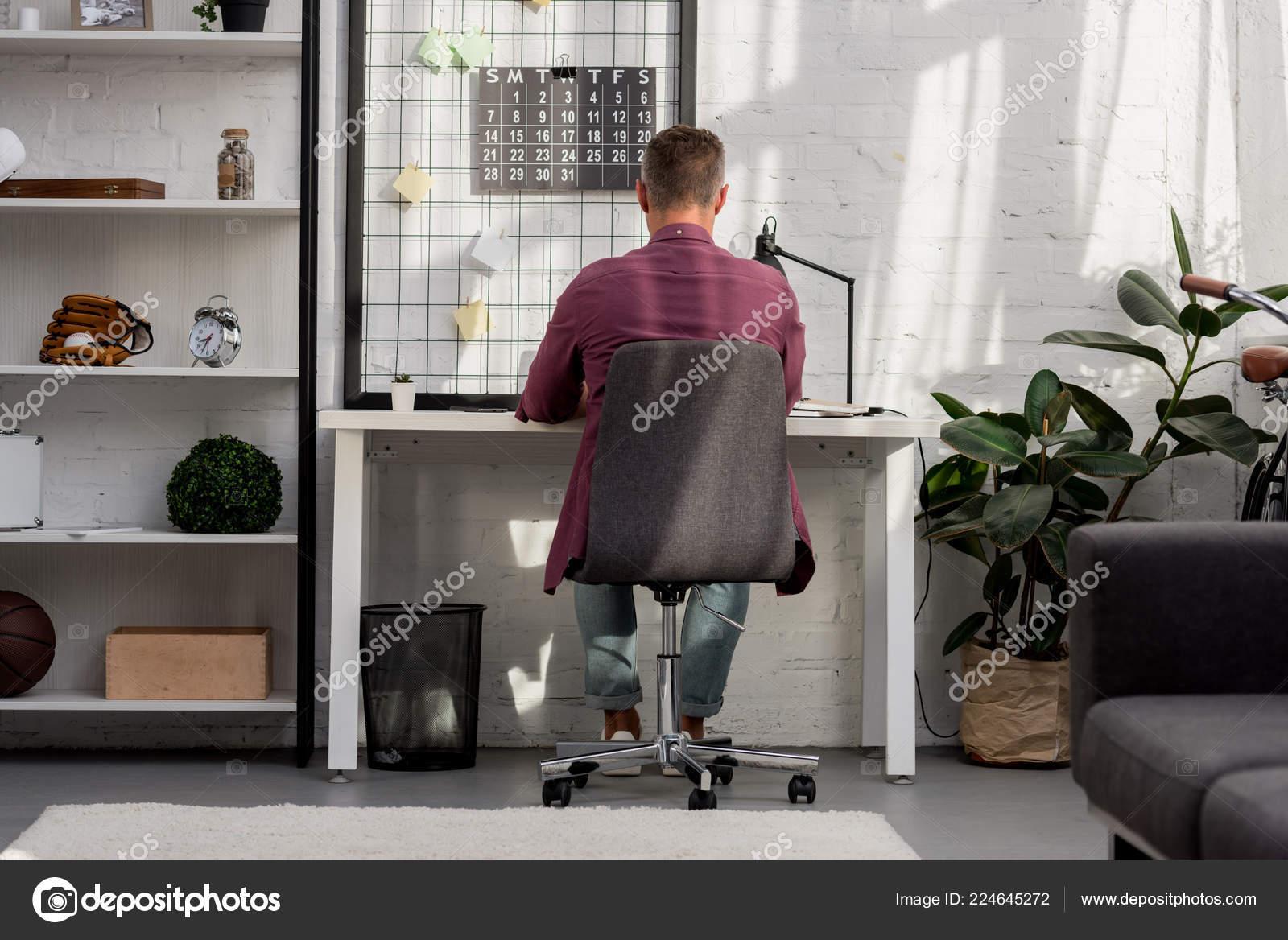 Ruckansicht Des Mann Auf Stuhl Sitzend Und Buro Hause Arbeiten