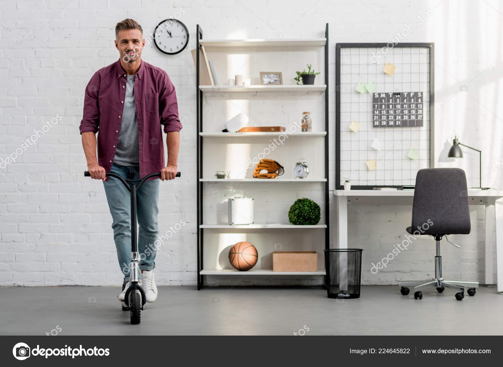Gut Aussehender Mann Reiten Scooter Hause Buro Stockfoto