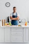 Fotografie pohledný muž v zástěře s rukama přes stojící v kuchyni