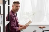 Fotografia uomo in piedi con il libro nelle mani a casa ufficio