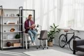 Fotografia bello che si siede sul tavolo e libro di lettura a casa ufficio