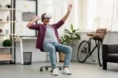 az ember ül a székre, és intett a virtuális-valóság sisak otthon, iroda