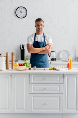 handsome man in apron with arms crossed standing at kitchen