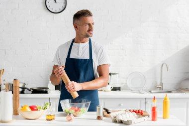 handsome adult man in apron salting salad at kitchen