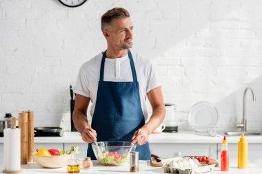 handsome man preparing salad at kitchen table