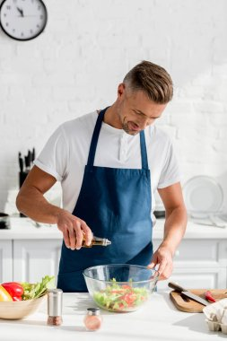 adult  man adding oil in salad at kitchen