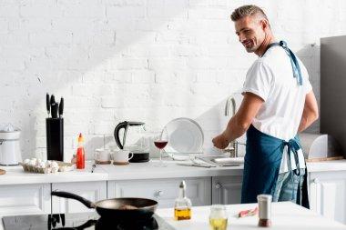 Adult man washing dishes at kitchen stock vector