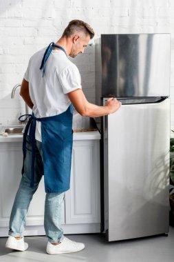 adult  man opening friedge door