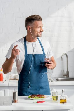 adult man in apron with glass of wine and cooked steak listening to music