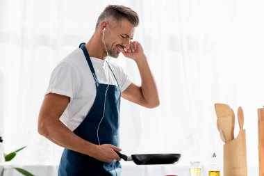 smiling man with earphones and pan in hand listening to music at kitchen