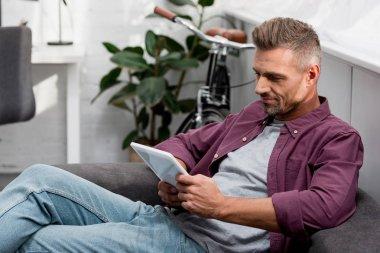 man sitting on sofa and using digital tablet