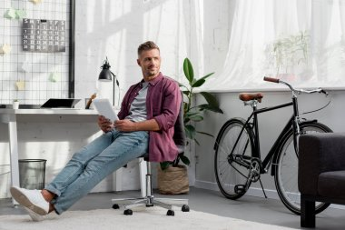 smiling man sitting on chair with digital tablet in hands