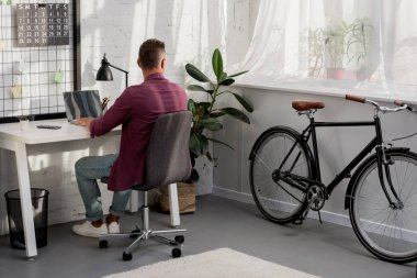 back view of man sitting at work place and looking out the window at home office