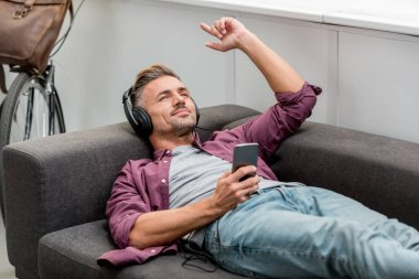 happy man listening music and singing while laying on sofa