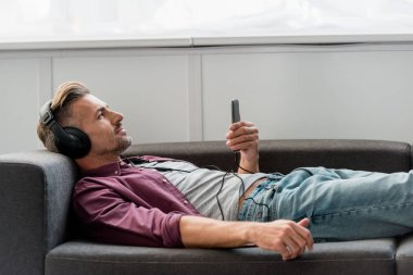 happy man with smartphone listening music while laying on sofa