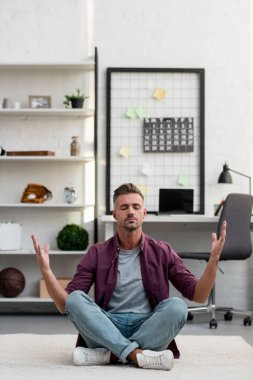 man sitting on floor and practicing yoga at home office