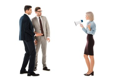 dissatisfied businesswoman speaking in megaphone and looking at colleagues isolated on white