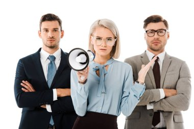 dissatisfied businesswoman holding megaphone while colleagues standing with arms crossed isolated on white