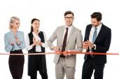 Fényképek mosolyogva vezető vágó piros szalag a nyitás, míg kollégái tapsolt, elszigetelt fehér