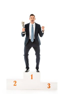excited emotional businessman with trophy cup standing on winners podium isolated on white