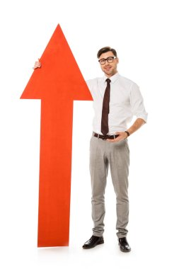Young handsome businessman standing with big red arrow isolated on white stock vector