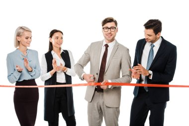smiling leader cutting red ribbon for grand opening while colleagues applauding, isolated on white