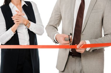 cropped view of businesspeople cutting red ribbon with scissors for grand opening, isolated on white
