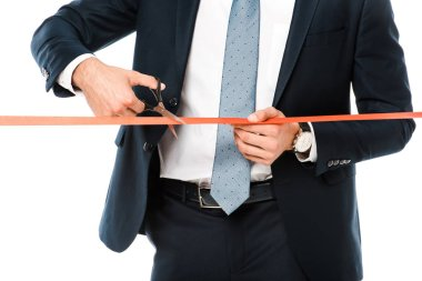 cropped view of businessman cutting red ribbon or tape with scissors for grand opening, isolated on white